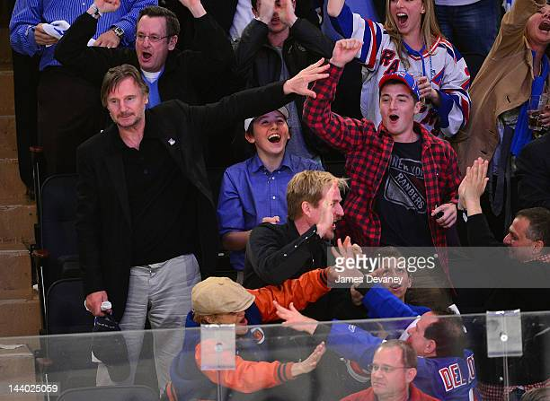 Liam Neeson guest and Daniel Neeson attend the Washington Capitals vs New York Rangers playoff game at Madison Square Garden on May 7 2012 in New...
