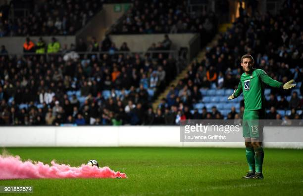 Liam O'Brien of Coventry City reacts to a smoke flare during The Emirates FA Cup Third Round match between Coventry City and Stoke City at Ricoh...