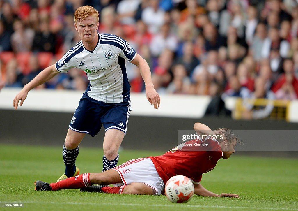 Liam O'Neil of WBA is challenged by Jorge Grant of Nottingham Forest during the pre season friendly match between Nottingham Forest and West Bromwich Albion at the City Ground on August 2, 2014 in Nottingham, England.