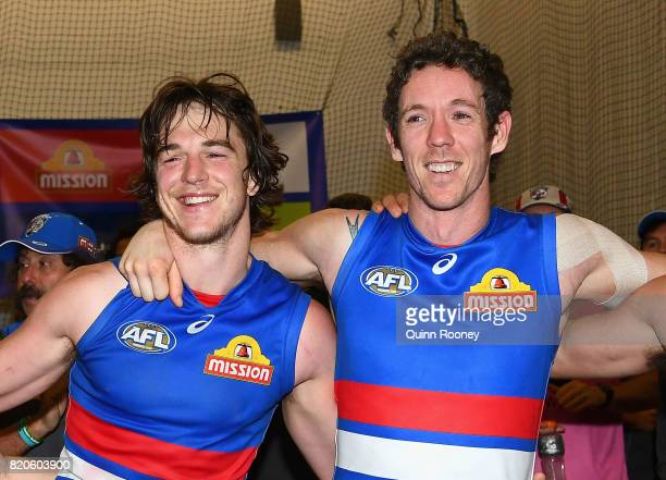 Liam Picken and Robert Murphy of the Bulldogs sing the song in the rooms after winning the round 18 AFL match between the Western Bulldogs and the...