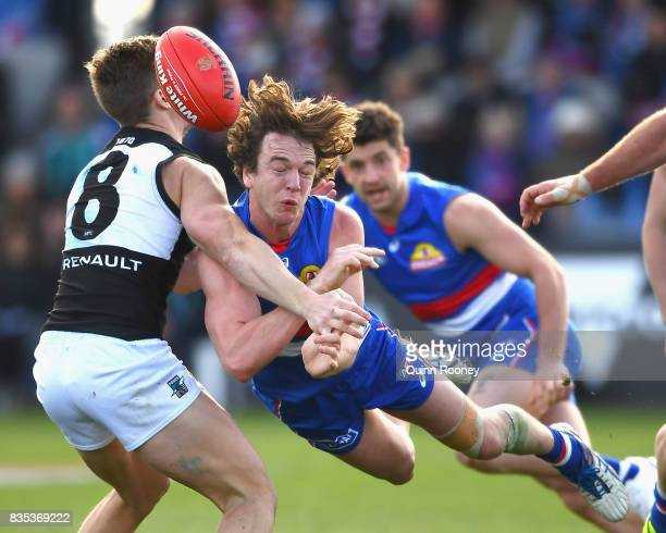 Liam Picken of the Bulldogs handballs whilst being tackled by Hamish Hartlett of the Power during the round 22 AFL match between the Western Bulldogs...