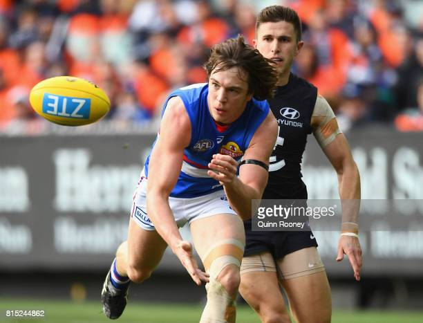 Liam Picken of the Bulldogs handballs whilst being tackled by Marc Murphy of the Blues during the round 17 AFL match between the Carlton Blues and...