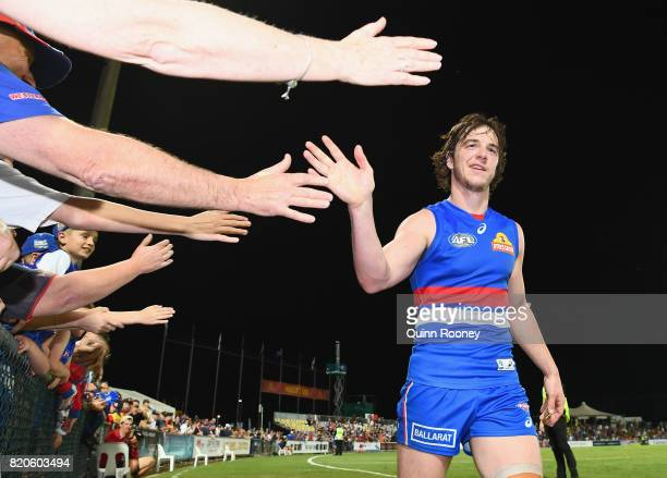 Liam Picken of the Bulldogs high fives fans after winning the round 18 AFL match between the Western Bulldogs and the Gold Coast Suns at Cazaly's...