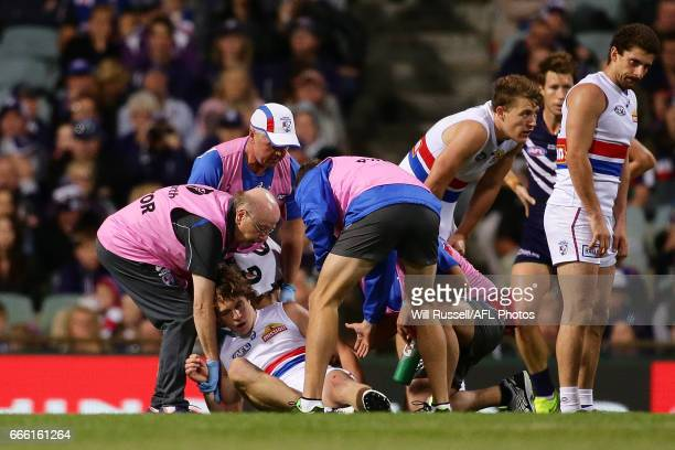 Liam Picken of the Bulldogs is assisted off the field after suffering concussion during the round three AFL match between the Fremantle Dockers and...