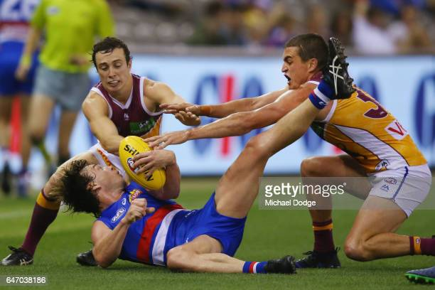 Liam Picken of the Bulldogs is tackled by Lewis Taylor and Tom Rockliff of the Lions during the 2017 JLT Community Series AFL match between the...