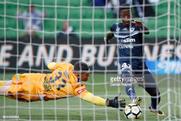 Liam Reddy of Perth Glory dives to defend Leroy George of the Victory during the round 16 ALeague match between the Melbourne Victory and Perth Glory...