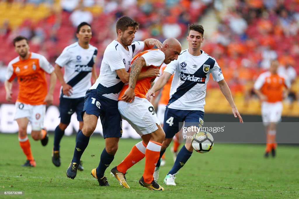 Liam Rose of the Mariners and Massimo Maccarone of the Roar compete for the ball during the round five A-League match between the Brisbane Roar and the Central Coast Mariners at Suncorp Stadium on November 5, 2017 in Brisbane, Australia.