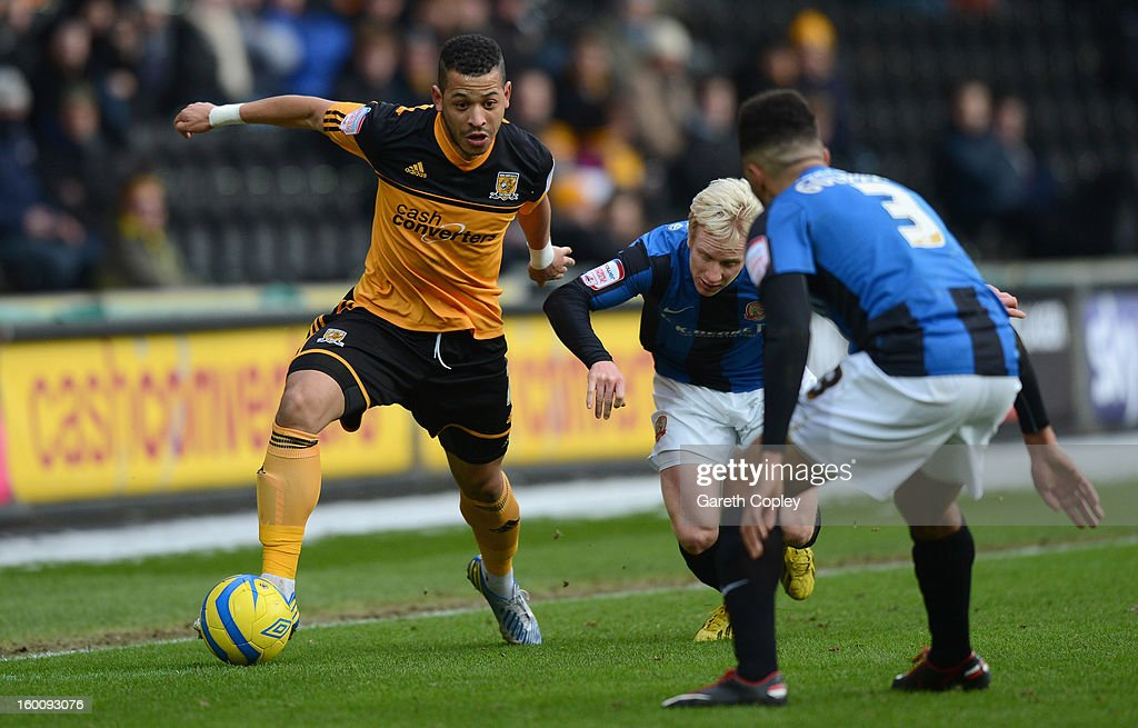 Liam Rosenior of Hull City gets past David Perkins and Scott Golbourne of Barnsley during the FA Cup Fourth Round between Hull City and Barnsley at KC Stadium on January 26, 2013 in Hull, England.