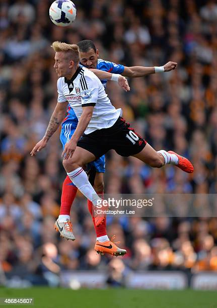 Liam Rosenior of Hull jumps with Lewis Holtby of Fulham during the Barclays Premier League match bewteen Fulham and Hull City at Craven Cottage on...