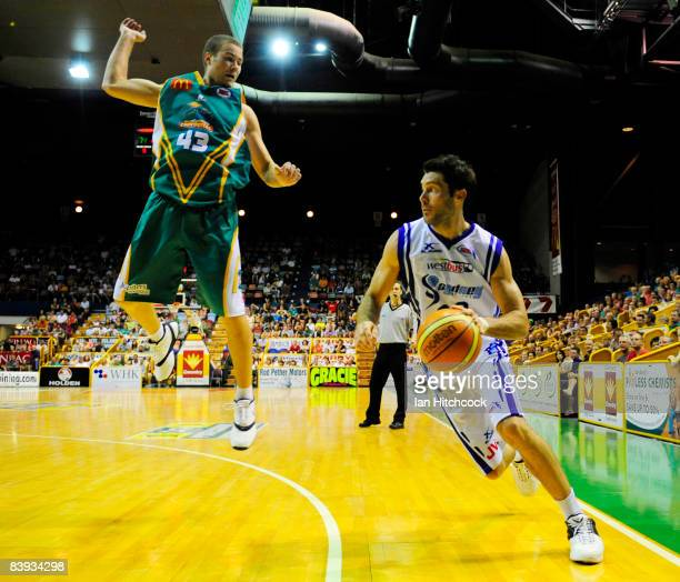 Liam Rush of the Spirit looks to gget past a leaping Brad Williamson of the Crocs during the round 12 NBL match between the Townsville Crocodiles and...