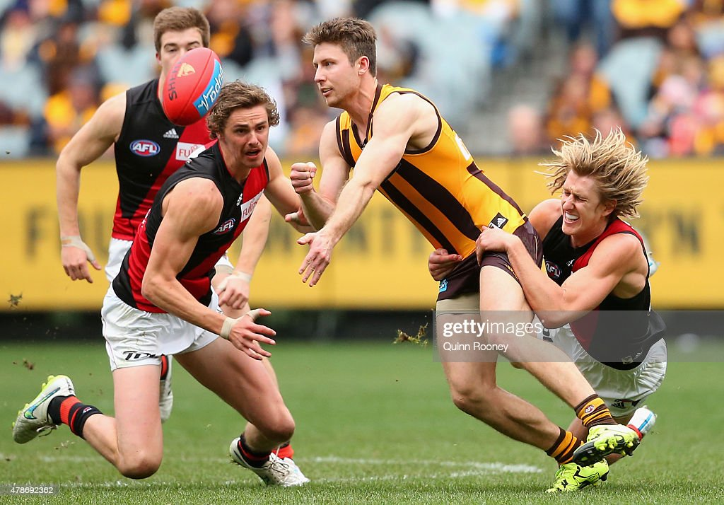 Liam Shiels of the Hawks handballs whilst being tackled by Dyson Heppell of the Bombers during the round 13 AFL match between the Hawthorn Hawks and the Essendon Bombers at Melbourne Cricket Ground on June 27, 2015 in Melbourne, Australia.