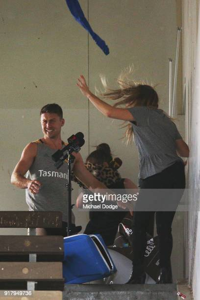 Liam Shiels of the Hawks helps evacuate the media conference location as a storm whips through during a Hawthorn Hawks AFL training session on...