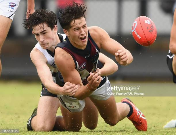 Liam Stocker of the Dragons handballs whilst being tackled during the round one TAC Cup match between Northern Knights and Sandringham at Frankston...