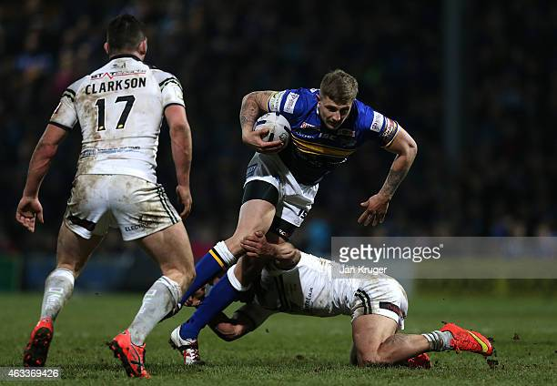 Liam Sutcliffe of Leeds Rhinos is tackled by Aaron Heremaia of Widnes Vikings during the First Utility Super League match between Leeds Rhinos and...