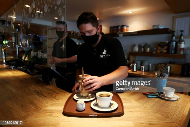 Liam Teague prepares hot drinks for customers at Zafiros bar on December 02, 2020 in Truro, England. Last night MPs voted in favour of government...