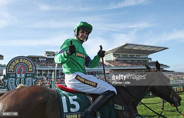 Liam Treadwell on Mon Mome celebrates after winning the John Smith's Grand National Steeple Chase Handicap on Mon Mome at Aintree on April 4 2009 in...