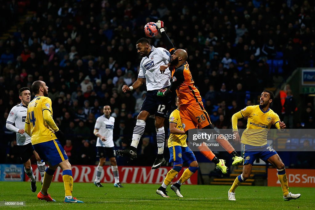 Liam Trotter (C) of Bolton in action with Ali Al Habsi of Wigan during the FA Cup Third Round match between Bolton Wanderers and Wigan Athletic at the Macron Stadium on January 3, 2015 in Bolton, England.
