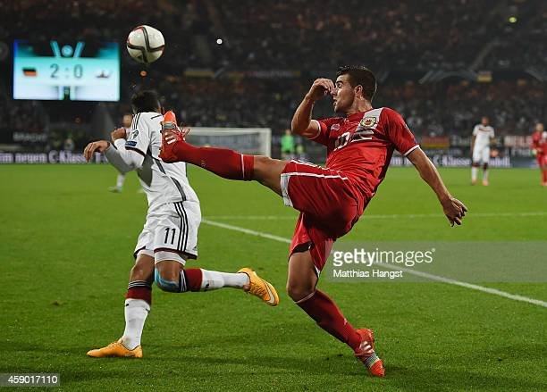 Liam Walker of Gibraltar is challenged by Karim Bellarabi of Germany during the EURO 2016 Group D Qualifier match between Germany and Gibraltar at...