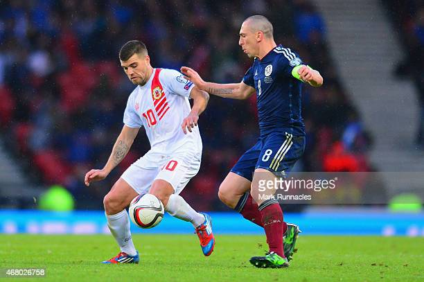 Liam Walker of Gibraltar is marshalled by Scott Brown of Scotland during the EURO 2016 Qualifier match between Scotland and Gibraltar at Hampden Park...