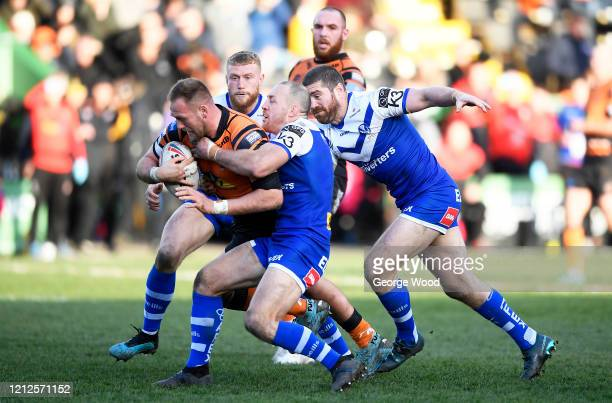 Liam Watts of Castleford is tackled by James Roby of St Helens during the Betfred Super League match between Castleford Tigers and St Helens at The...