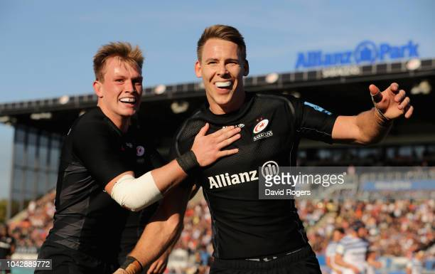 Liam Williams of Saracens celebrates with team mate Nick Tompkins after scoring his third try during the Gallagher Premiership Rugby match between...