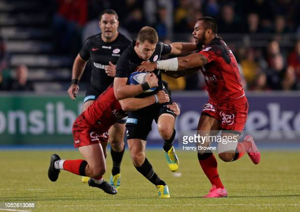 Liam Williams of Saracens is tackled by Rudi Wulf and Adrien Seguret of Lyon during the Champions Cup match between Saracens and Lyon Olympique...