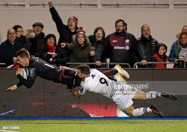 Liam Williams of Saracens scores a try despite the efforts of Thomas Habberfield of Ospreys during the European Rugby Champions Cup match between...