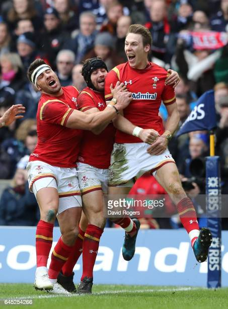 Liam Williams of Wales celebrates with teammates Leigh Halfpenny and Rhys Webb after scoring the opening try during the RBS Six Nations match between...