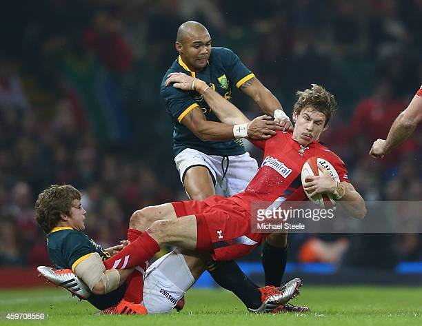 Liam Williams of Wales holds onto the ball as Pat Lambie and Cornal Hendricks of South Africa challenge during the International match betwwen Wales...