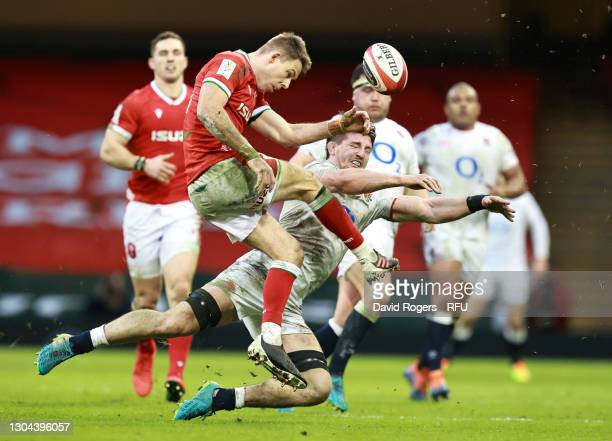 Liam Williams of Wales kicks upfield as Tom Curry of England charges down during the Guinness Six Nations match between Wales and England at...
