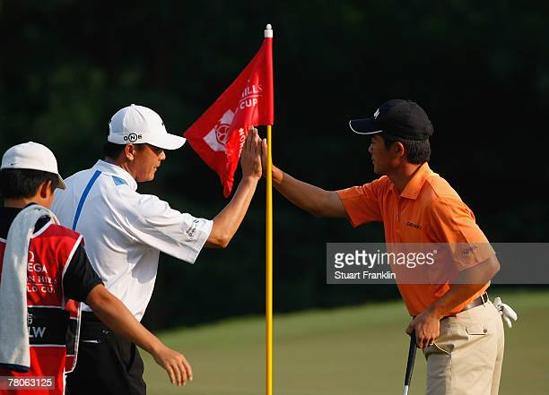 Lian Wei Zhang and Wen Chong Liang of China celebrate on the 16th hole during the first round of the Omega Mission Hills World Cup at the Mission...