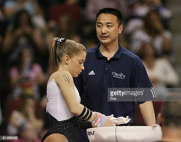 Liang Chow talks with Shawn Johnson before her routine on the uneven parallel bars during day 3 of the Visa Championships at Agganis Arena June 7,...