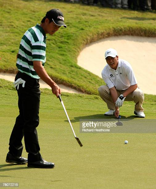 Liang WenChong and Zhang LianWei of China line up a putt on the 4th green during the second round of the Omega Mission Hills World Cup at the Mission...