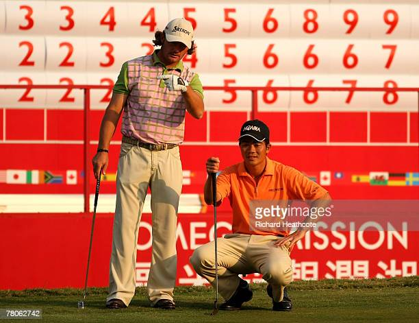 Liang WenChong of China and Alex Cejka of Germany line putts up on the 18th green during the first round of the Omega Mission Hills World Cup at the...