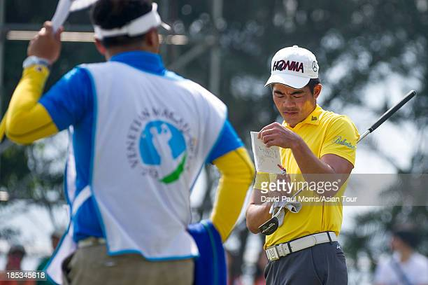 Liang Wenchong of China checks his map of the 18th green during round three of the Venetian Macau Open on October 19 2013 at the Macau Golf Country...