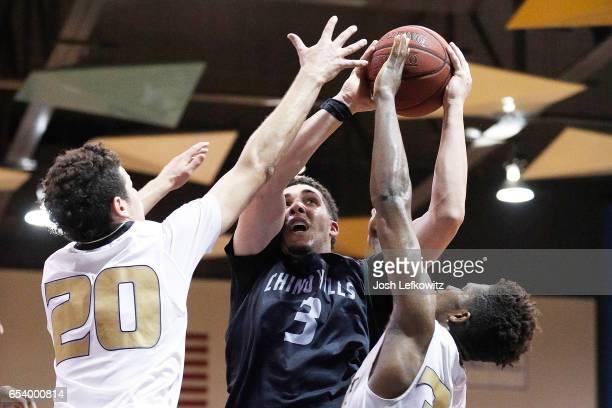 LiAngelo Ball of Chino Hills High School powers through Jordan Schakel and David Singleton of Bishop Montgomery High School as he shoots during the...