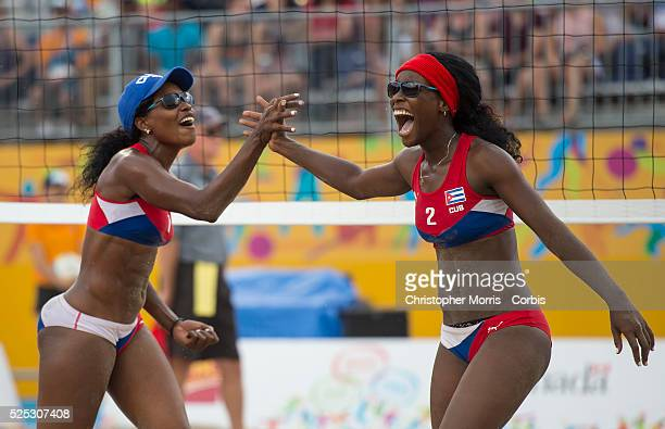Lianma Flores and Leila Martinez of Cuba celebrate their victory during Canada vs Cuba in beach volleyball competition at the 2015 PanAm Games in...