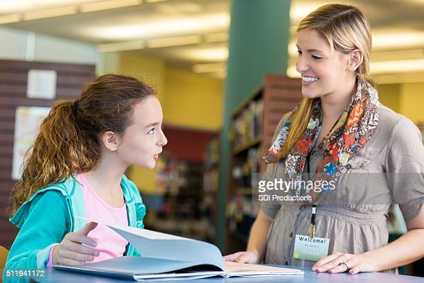 Libarian helping elementary age student in public library