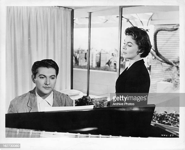 Liberace at the piano with Joanne Dru in a scene from the film 'Sincerely Yours' 1955