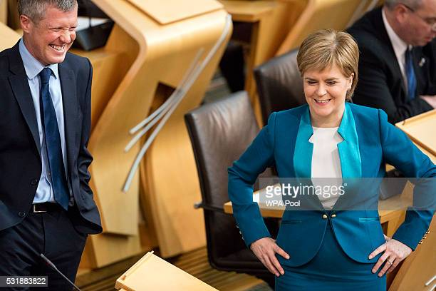 Liberal Democrat leader in Scotland Willie Rennie chats with First Minister of Scotland Nicola Sturgeon in the Scottish parliament before Ms Sturgeon...