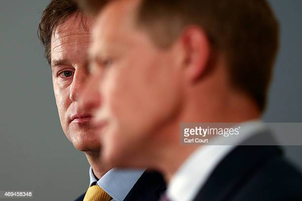 Liberal Democrat leader Nick Clegg looks on as Chair of the Liberal Democrat Manifesto Group David Laws speaks during a press conference in which the...