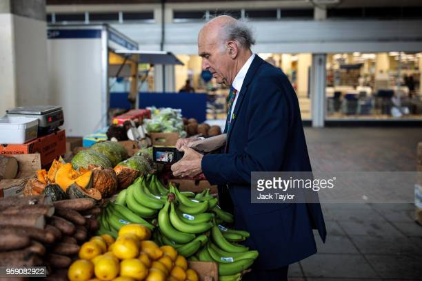 Liberal Democrat Leader Vince Cable buys a mango from a fruit and vegetable stall in Catford Market as the party launch their Lewisham East...