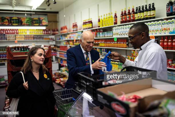 Liberal Democrat Leader Vince Cable buys some bananas from a shop as Liberal Democrat Parliamentary candidate for Lewisham East Lucy Salek looks on...