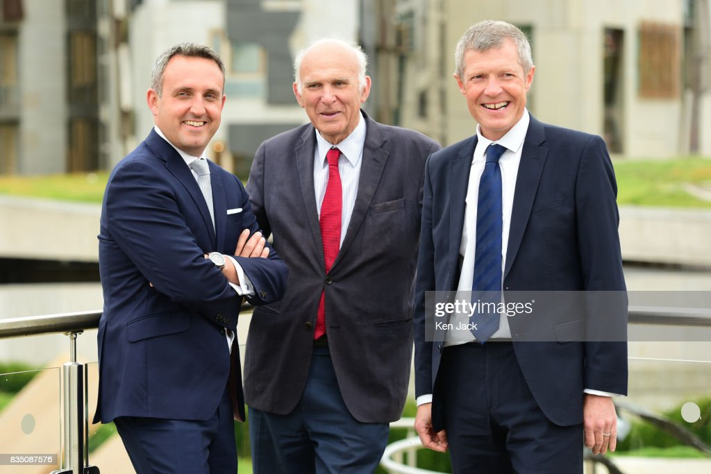 Liberal Democrat leader Vince Cable (C) Scottish party leader Willie Rennie (R) and Alex Cole-Hamilton MSP chat together after posing for photographs with the Scottish Parliament in the background ahead of a Scottish Liberal Democrat party event, on August 18, 2017 in Edinburgh, Scotland.