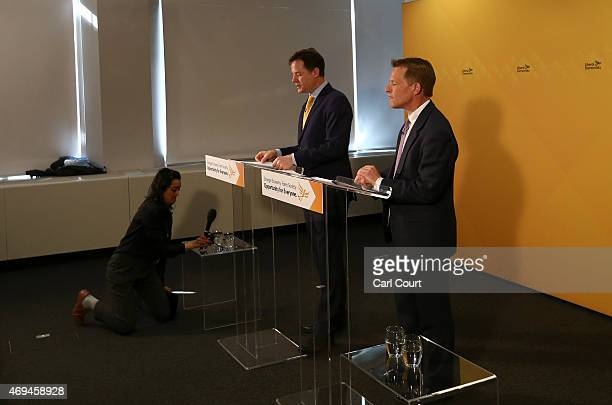 Liberal Democrat party member adjusts a microphone during sound problems as leader Nick Clegg and Chair of the Liberal Democrat Manifesto Group David...