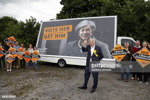 Liberal Democrat politician Vince Cable gestures to the media while unveiling a campaign poster featuring a combined image of Nigel Farage and...