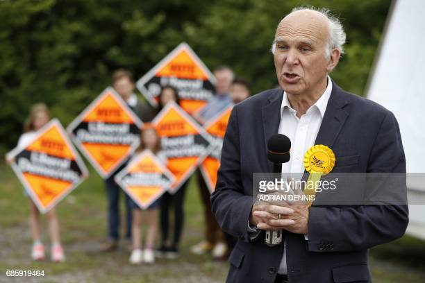 Liberal Democrat politician Vince Cable records an interview after unveiling a campaign poster featuring a combined image of Nigel Farage and Theresa...