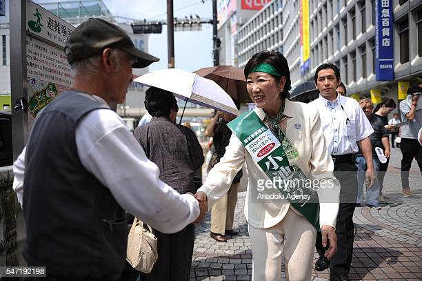 Liberal Democratic Party lawmaker and former defense minister Yuriko Koike greets people as she kicks off her campaign for the July 31 Tokyo...