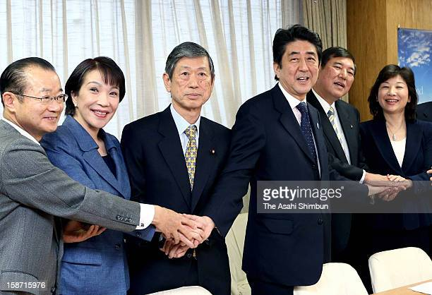 Liberal Democratic Party President Shinzo Abe shakes hands with election bureau chief Tateo Kawamura policy chief Sanae Takaichi vice president...