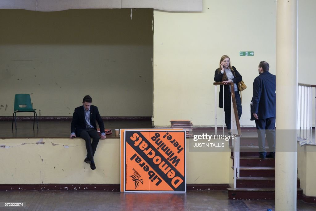 Liberal Democratic Party supporters clear up after a campaign event in London on April 24, 2017, in the build-up to the general election on June 8th. Tim Farron, whose centre-left party holds just nine seats, hopes to make gains in the surprise election in June. / AFP PHOTO / Justin TALLIS